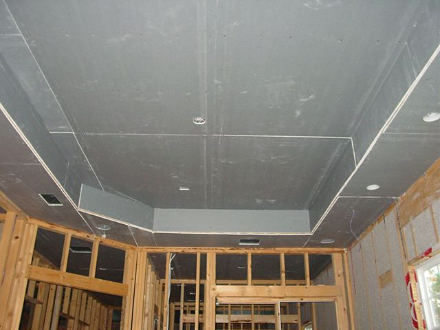 A two-level ceiling of plasterboard with their hands