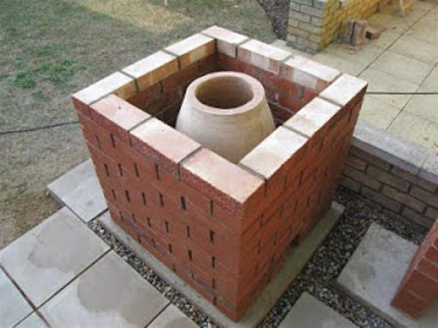 The space between themselves tandyr and external brick walls filled with thermal storage materials