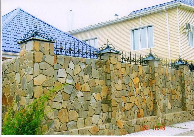 Grouting and wiping of the surface - the final works on the construction of a fence made ​​of natural stone