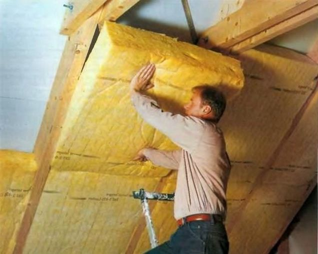 Laying the mats of mineral wool between the rafters