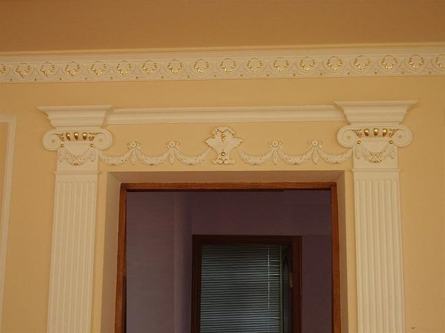 Stucco on the perimeter of the opening without a door - columns with pilasters and capitals .