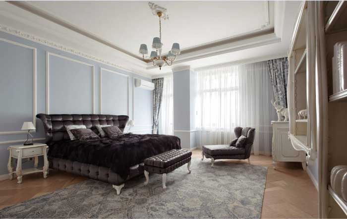 Interior design bedroom in a classic style .Large dark bed and couch .