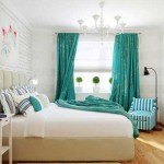The curtains in the bedroom aqua .The walls of the bedroom are covered with clapboard , painted white