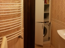 Corner cabinet made ​​of white chipboard for a washing machine in the bathroom