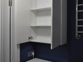 White wall cabinet with three shelves above the washing machine in the bathroom