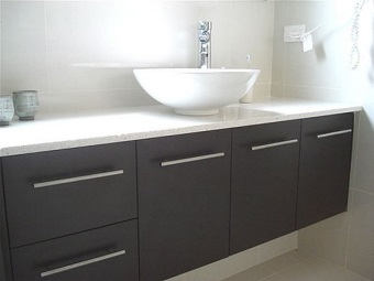 Black cabinet with a white top and white overhead washbasin