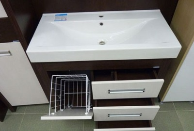 Wooden cabinet with a sink in the bathroom and built-in laundry basket