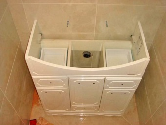 Installing cabinets with sink and laundry basket