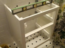Installation of hanging cabinets with a sink in the bathroom with their hands