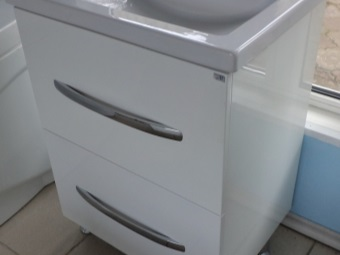 White floor cupboard on metal legs with built-in sink