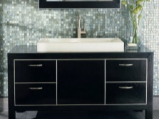 Black floor stand on legs with metal handles on the drawers and a large built-in white sink