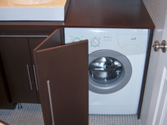 Wooden cabinet with a sink and a door which closes the washing machine