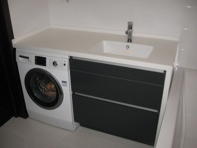 Plastic black and white pedestal sink with a washing machine