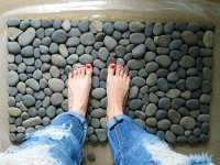 Bath mat with your hands from sea stones