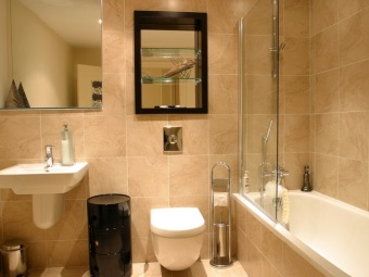 The interior of the bathroom , room with WC - bath with a glass partition , mounted sink and toilet
