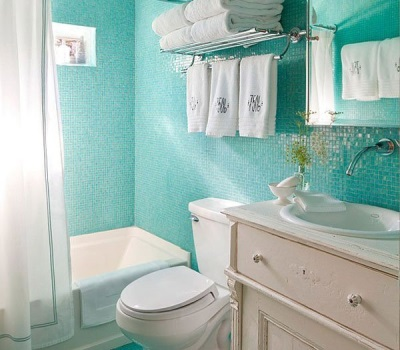 Turquoise mosaic in the interior of the bathroom , room with WC with white furniture and fixtures