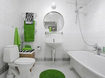 The interior of the white bathroom with WC with bright accents in the form of a green towel and mat