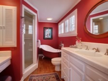 Red bathroom interior , combined with a toilet with white furniture and fixtures
