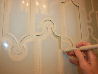 The application of paint on the stencil pattern in a bathroom with a brush