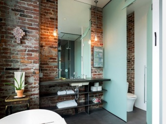 Bathroom in the loft -style - brick walls without decoration , glass partitions , large mirror