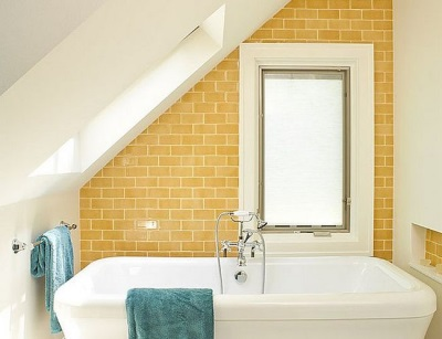 Bathroom in loft style with brick and white-washed walls , with bright accents in the form of colored towels