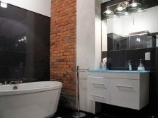 Backlit mirror in the bathroom in the loft style combined with brick walls