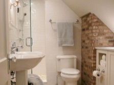 Combined walls of brick , stucco and tile in the bathroom in the loft