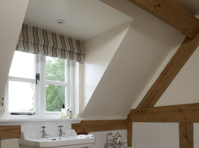 Wooden beams on the plastered walls and ceiling in the bathroom loft style