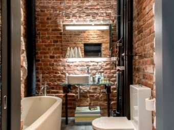 Brick walls , white bathroom fixtures and glass furniture in the bathroom in the loft