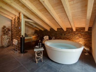 Bathroom in chalet style - wooden ceilings , a large bath , stone walls and floors