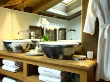 Wooden cabinet with sinks made ​​of stone in the bathroom in chalet style,