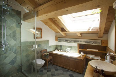 Green tiles on the walls in the bathroom in chalet style,