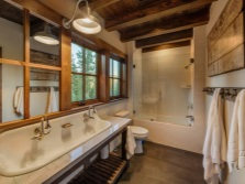 Wooden ceilings, a single metal lamp, whitewashed walls , stone floors - a bathroom in chalet style