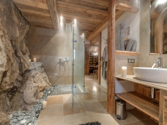Stone floors and walls , wooden furniture in the bathroom in chalet style,