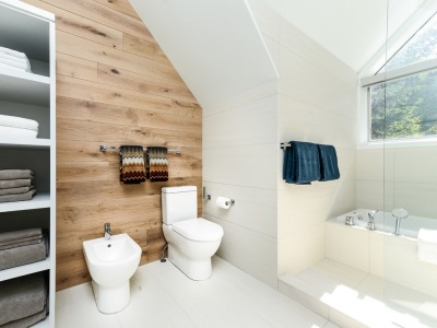 Bathroom in a Scandinavian style - walls of real wood , white tub , white ceiling , towels with the national pattern and Scandinavian