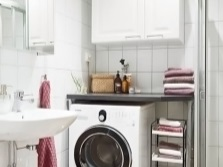 A small bathroom with shower and washing machine