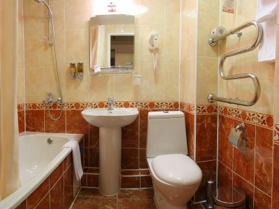 A small bathroom with white sanitary ware and towels