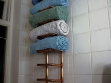 Water heated towel rail with shelves