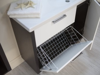 Cabinet with sink and laundry basket in the bathroom