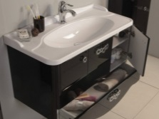 Bedside table with drawers and a sink in the bathroom